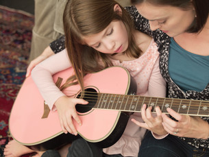 Mid adult woman teaching daughter to play acoustic guitarの写真素材 [FYI03614223]