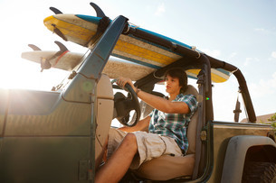 Teenager driving jeep with surfboardsの写真素材 [FYI03614268]
