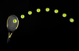 Tennis racket and balls in motionの写真素材 [FYI03614279]