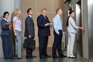 Businesspeople waiting in queue for elevatorの写真素材 [FYI03614283]