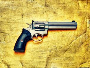 Hand gun against yellow backgroundの写真素材 [FYI03614300]