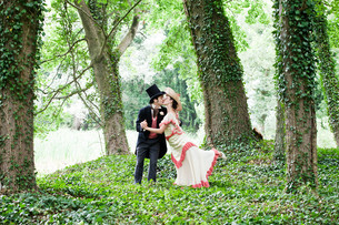 Bridal couple in 1920s style clothing, kissing in parkの写真素材 [FYI03614387]