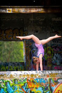 Gymnast performing with graffiti on wallの写真素材 [FYI03614446]