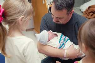 Father cradling newborn baby girl with two older sistersの写真素材 [FYI03614469]