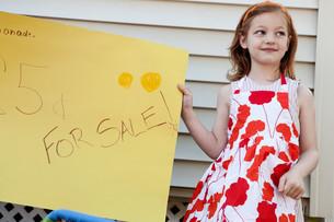 Girl holding homemade lemonade for sale signの写真素材 [FYI03614473]
