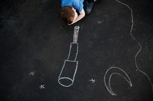 Boy on floor looking at chalk drawingの写真素材 [FYI03614480]