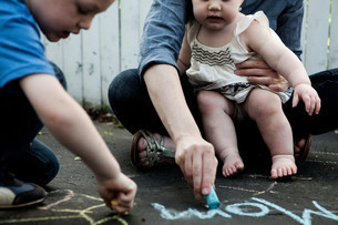 Mother and two children writing on floor with chalkの写真素材 [FYI03614481]