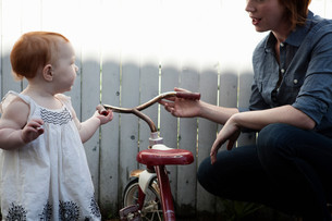 Mother helping baby daughter with tricycleの写真素材 [FYI03614485]