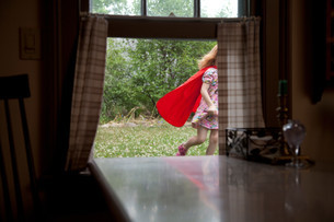 Girl in a cape running past an open windowの写真素材 [FYI03614506]