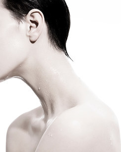 Woman with liquid droplets on neckの写真素材 [FYI03614521]