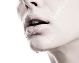 Woman with liquid droplets on lips, close upの写真素材 [FYI03614523]