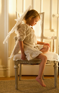 Little girl on chair dressed as angelの写真素材 [FYI03614541]