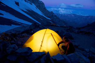Woman unzips her tent at Camp One on Aconcagua in the Andesの写真素材 [FYI03614557]