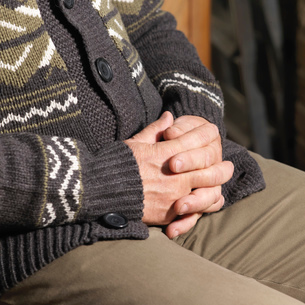 Older man sitting with hands foldedの写真素材 [FYI03614790]