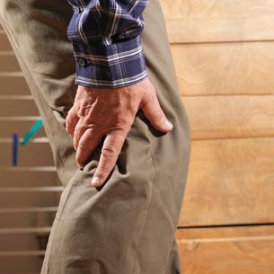 Older man rubbing back of his kneeの写真素材 [FYI03614791]