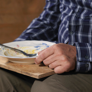 Older man eating on trayの写真素材 [FYI03614794]