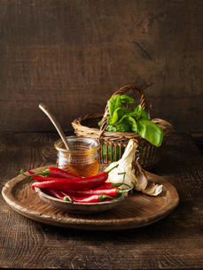Chilis, honey, garlic and basil on boardの写真素材 [FYI03614848]