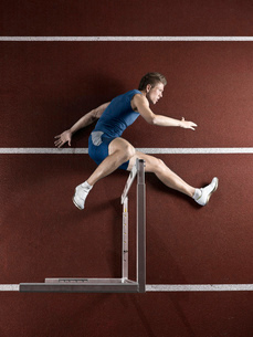 Runner laying with hurdle on trackの写真素材 [FYI03614875]