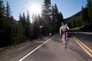 Cyclist biking on rural roadの写真素材 [FYI03614960]
