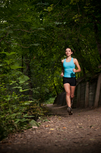 Woman running on dirt pathの写真素材 [FYI03615026]