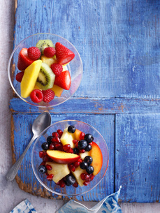 Bowls of fruit salad on wooden boardの写真素材 [FYI03615054]