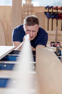 Craftsman preparing planks of wood in workshopの写真素材 [FYI03615379]