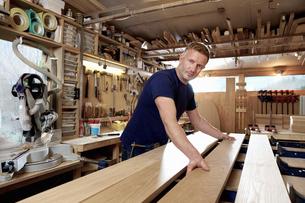 Craftsman preparing planks of wood in workshopの写真素材 [FYI03615380]