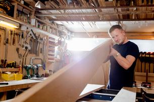 Craftsman preparing planks of wood in workshopの写真素材 [FYI03615381]