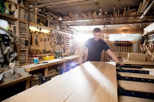 Craftsman preparing planks of wood in workshopの写真素材 [FYI03615382]