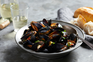 Bowl of garlic mussels with glass of white wineの写真素材 [FYI03615403]