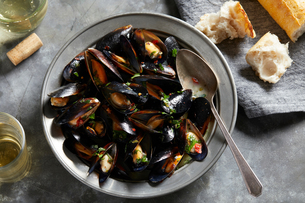 Bowl of garlic mussels with glass of white wine, overhead viewの写真素材 [FYI03615406]
