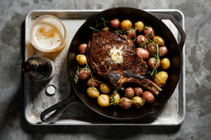 Skillet with large tomahawk steak & potatoes, overhead viewの写真素材 [FYI03615422]