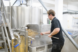 Master brewer raking out spent hops and ingredients in small breweryの写真素材 [FYI03615441]