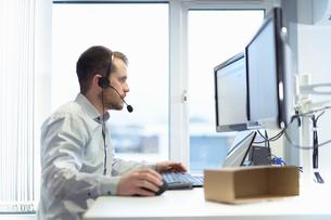 Worker taking customer calls in design department of cardboard box factoryの写真素材 [FYI03615447]