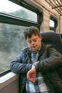 Man with down syndrome checking time on trainの写真素材 [FYI03615507]