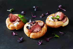 Still life with canapes of roast beef in yorkshire puddings on black slateの写真素材 [FYI03615532]