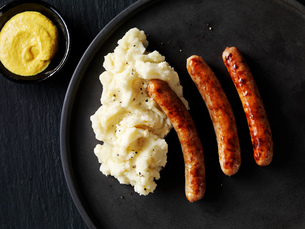 Still life with sausages and mash on black plate with bowl of  mustard, overhead viewの写真素材 [FYI03615538]