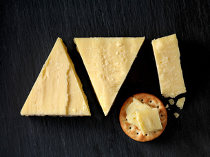 Still life with cheese cracker and cheddar cheese triangles on black slate, overhead viewの写真素材 [FYI03615540]