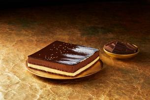 Still life with triple chocolate dessert on gold plate, christmas dessertの写真素材 [FYI03615542]