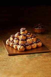 Still life with stacked chocolate profiteroles on gold plate, christmas dessertの写真素材 [FYI03615544]