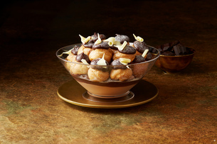 Still life with chocolate profiteroles on gold plate, christmas dessertの写真素材 [FYI03615545]