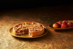 Still life with plum and almond tart on gold plate, christmas dessertの写真素材 [FYI03615546]