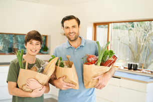 Boy and his father in kitchen holding grocery bags, portraitの写真素材 [FYI03615583]