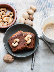 Walnuts in shell, cashew nuts, cake slices and coffeeの写真素材 [FYI03615702]