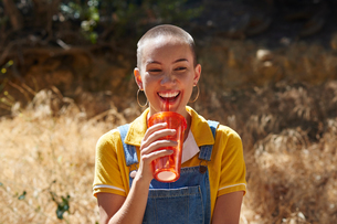 Teenage girl with cropped hair drinking from takeaway cup in park, Los Angeles, California, USAの写真素材 [FYI03615843]