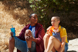 Young man and female friend drinking from takeaway cups in park, Los Angeles, California, USAの写真素材 [FYI03615844]