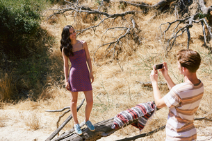 Young man photographing girlfriend in park, Los Angeles, California, USAの写真素材 [FYI03615849]