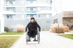 Woman in wheelchair in residential areaの写真素材 [FYI03616012]