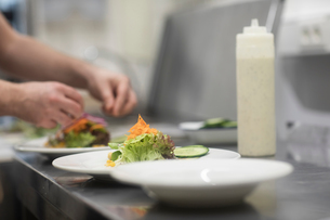 Fast food worker adding salad to hamburger in commercial kitchen, detail of handの写真素材 [FYI03616014]