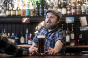 Barman serving beer to customer at bar in traditional Irish public houseの写真素材 [FYI03616034]